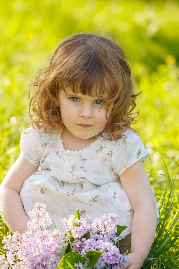 Liten flicka i en solig trädgård fotografering för bildbyråer