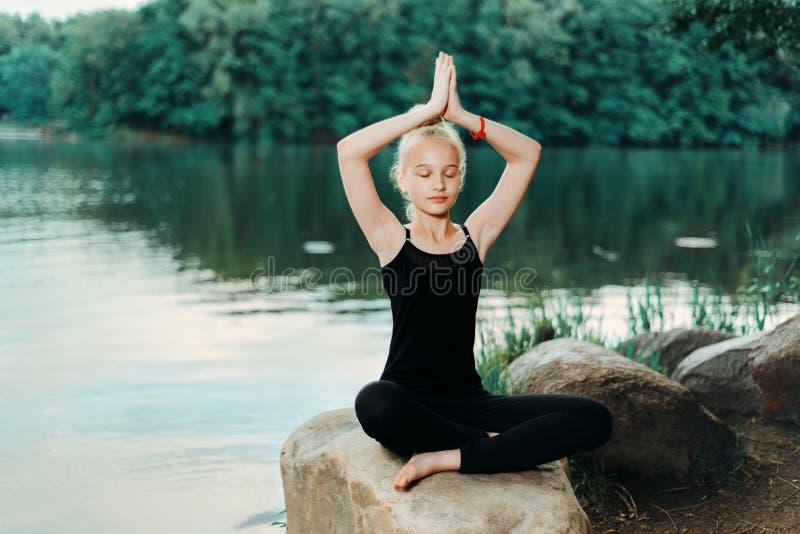 Liten flicka i en svart T-tröja som gör yoga royaltyfria bilder