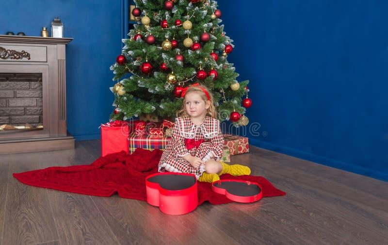 Liten flicka i ett härligt klänninganseende nära julträd med gåvan arkivbilder