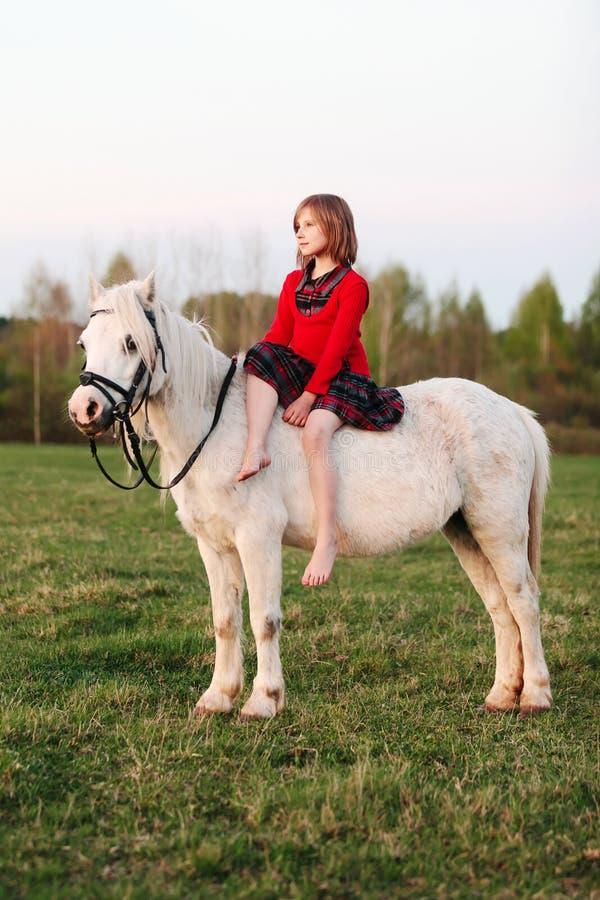 Liten flicka i ett klänningsammanträde på en vit häst och blickar in i avståndet arkivbild