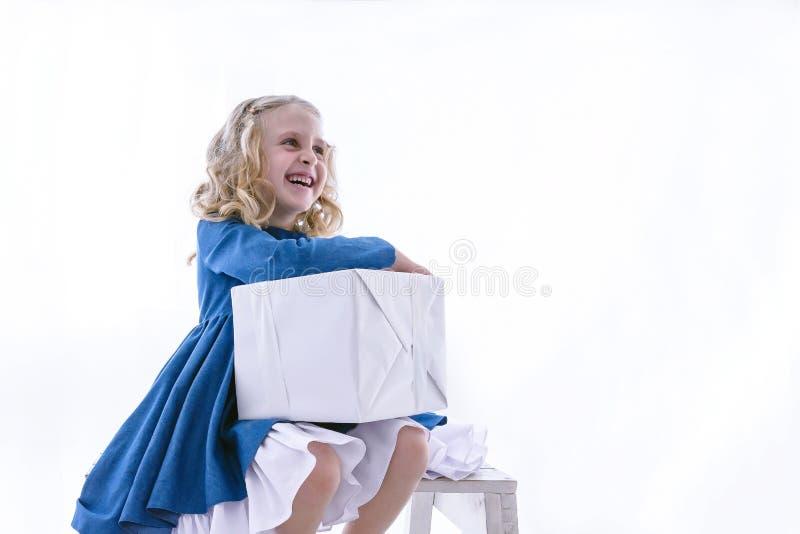 Liten flicka i ett ljuvt lynne med en gåva, vit ask på en vit bakgrund arkivbild