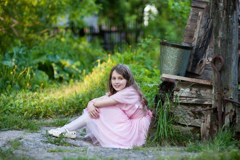 Liten flicka i ett rosa klänningsammanträde nära brunnen arkivfoto
