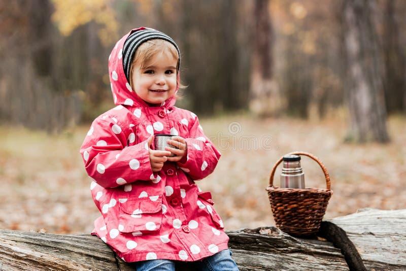 Liten flicka i ett sammanträde för ärtaomslag på ett träd och ett drickate arkivfoto