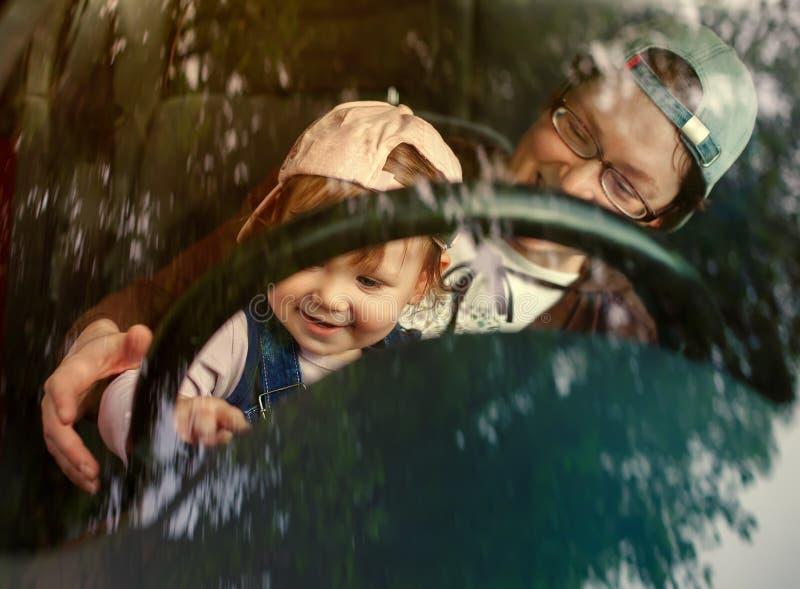 Liten flicka i förarsätet av en bil royaltyfri bild