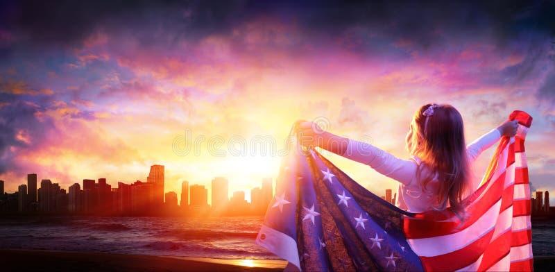 Liten flicka i frihet med amerikanska flaggan royaltyfria bilder