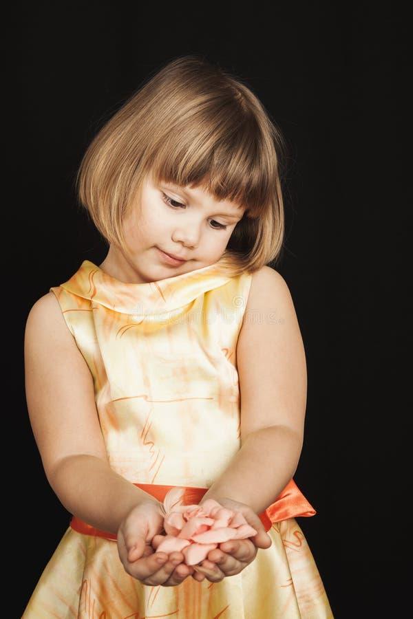 Liten flicka i gul klänning med rosa färgrosblomman royaltyfria bilder