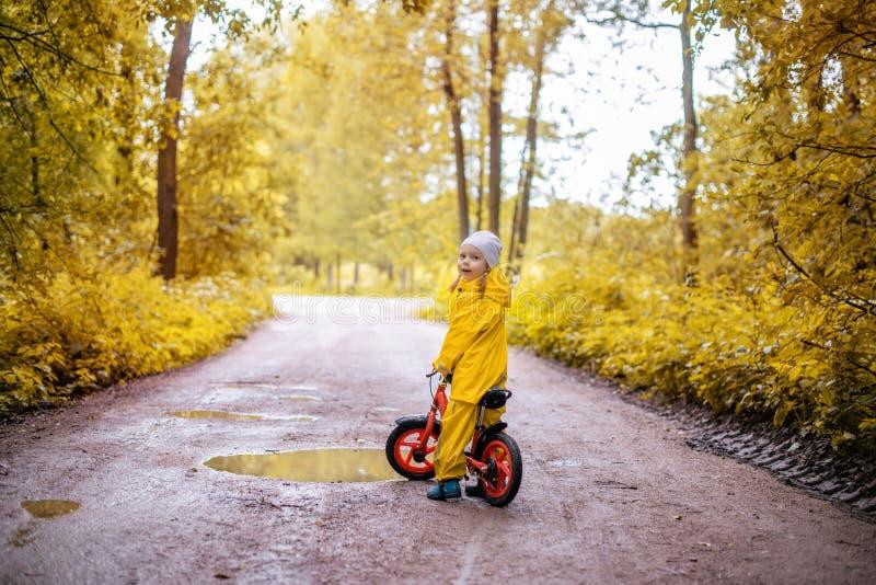 Liten flicka i gul vattentät kläder med cykeln royaltyfri foto