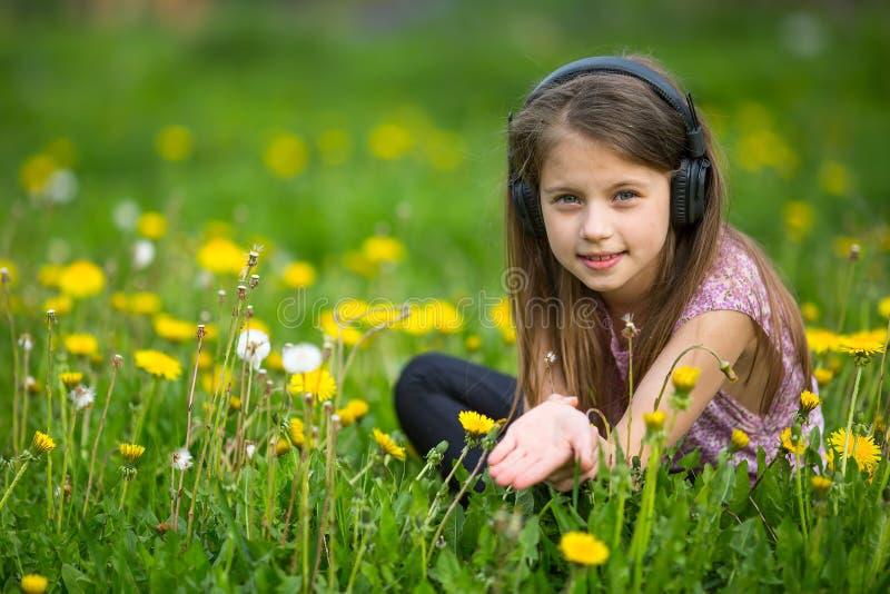 Liten flicka i hörlurar som sitter på det gröna gräset i parkera arkivbilder