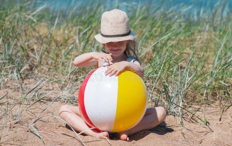 Liten flicka i hatten som spelar på stranden med bollen, solig sommardag arkivbild