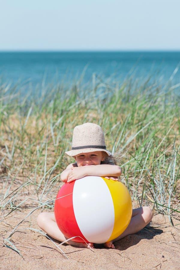 Liten flicka i hatten som spelar på stranden med bollen, solig sommardag arkivfoton