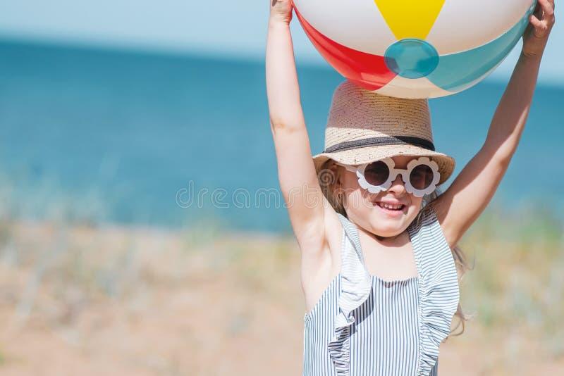 Liten flicka i hatten som spelar på stranden med bollen, solig sommardag arkivbilder
