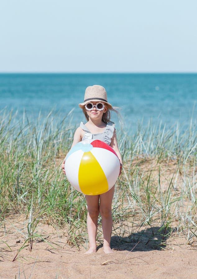 Liten flicka i hatten som spelar på stranden med bollen, solig sommardag arkivfoto