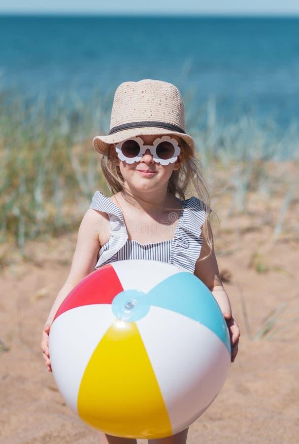 Liten flicka i hatten som spelar på stranden med bollen, solig sommardag royaltyfri fotografi