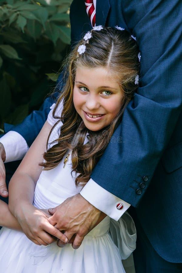 Liten flicka i hennes första nattvardsgångdag med hennes fader royaltyfria bilder