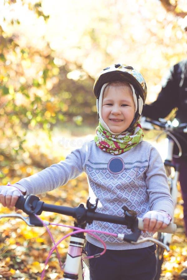 Liten flicka i hjälmen med cykeln i höstskogen arkivbilder