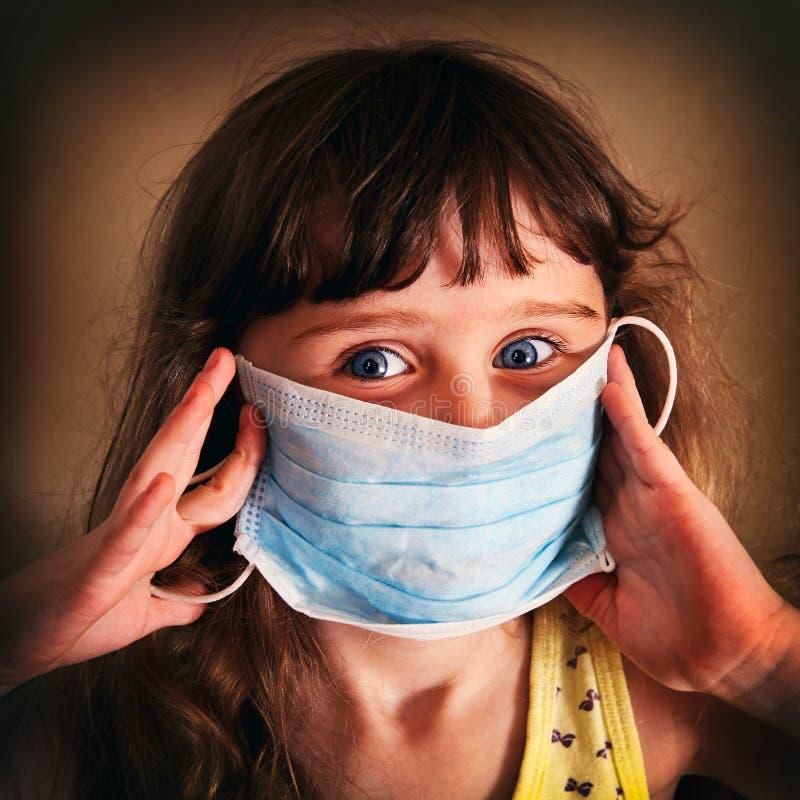 Liten flicka i influensamaskering arkivfoton