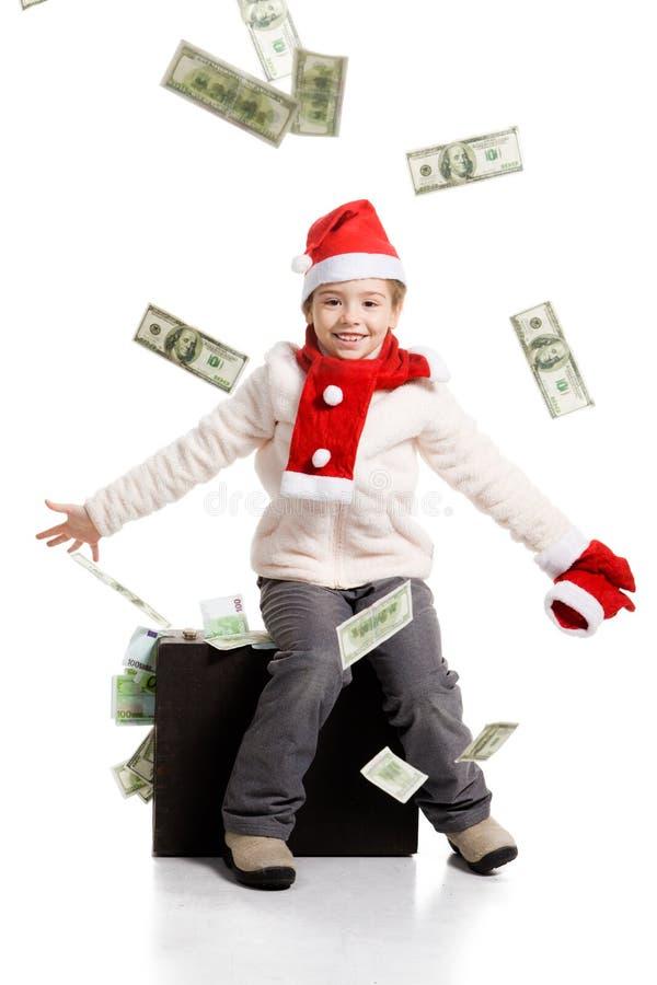 Liten flicka i jultomten hatt och resväska med pengar fotografering för bildbyråer