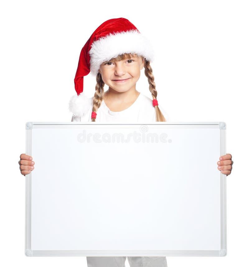 Liten flicka i jultomtenhatt med det tomma brädet royaltyfri bild