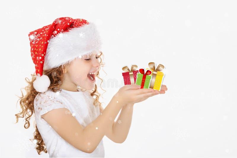 Liten flicka i jultomtenhatten, hålljulgåva i hans hand royaltyfria foton