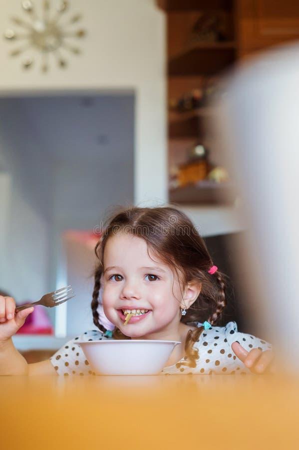 Liten flicka i köket som ler som äter spagetti royaltyfria foton