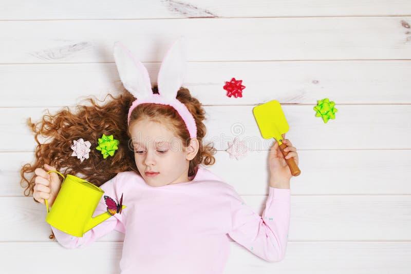 Liten flicka i kaninöron som ligger på trägolvet royaltyfria foton