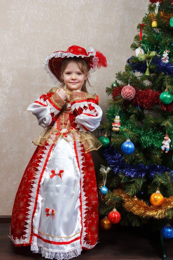 Liten flicka i karnevaldräkt nära julgranen arkivbilder
