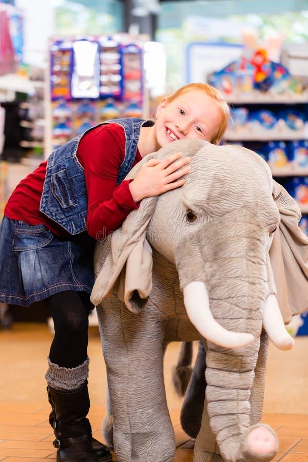 Liten flicka i kel för leksaklager med det välfyllda djuret arkivfoto