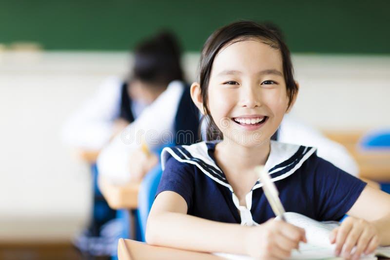 Liten flicka i klassrum och hennes vänner i bakgrund royaltyfria bilder