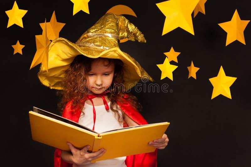 Liten flicka i läsebok för himmeliakttagaredräkt arkivfoto