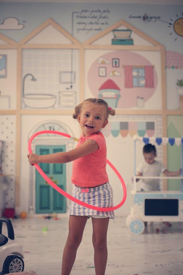 Liten flicka i lekrummet Den förskole- flickan spelar med ho arkivbild