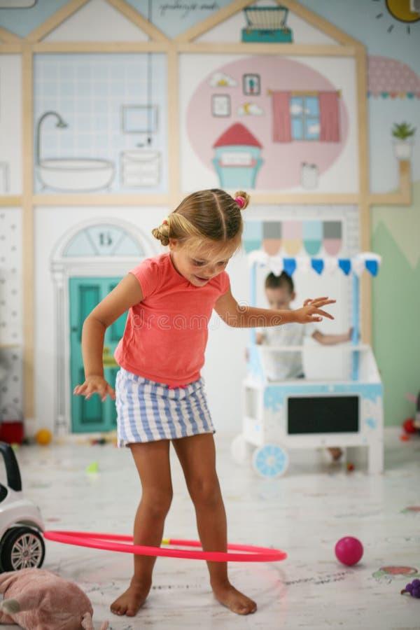 Liten flicka i lekrummet Den förskole- flickan spelar med ho royaltyfri fotografi