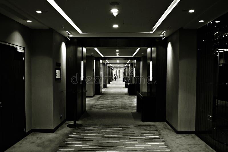 Liten flicka i mörkt korridorer och ljus i byggnaden svart white royaltyfri fotografi