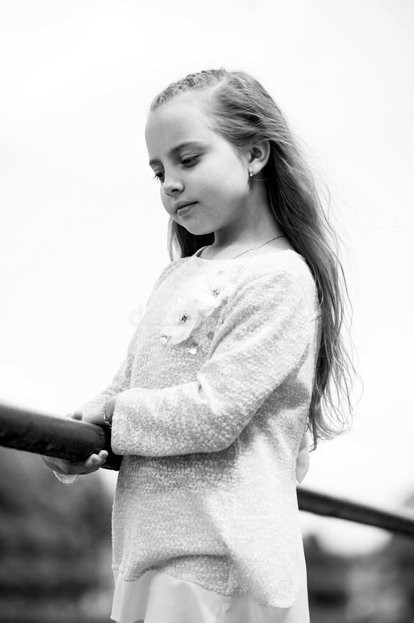 Liten flicka i moderiktig kläder på naturlig bakgrund Barn med utomhus- långt blont hår Ungemodell i trendig klänning royaltyfria foton