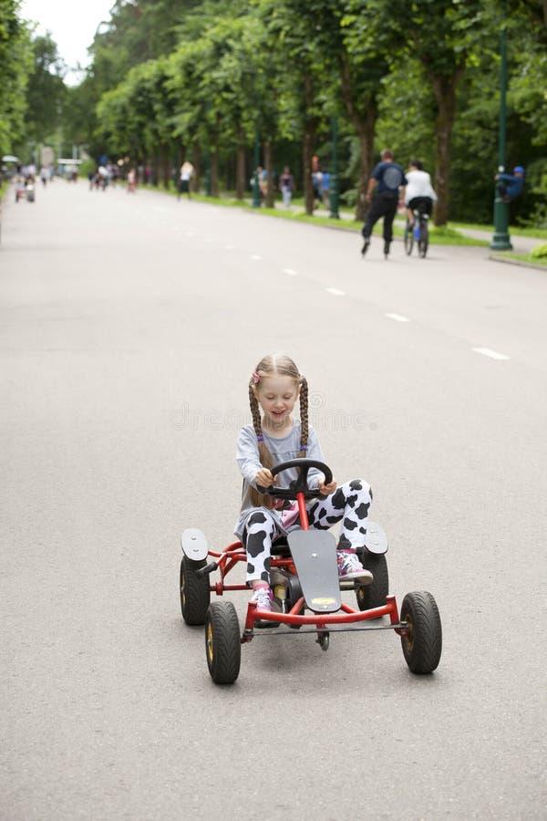 Liten flicka i nöjesfält för tävlings- bil arkivfoton