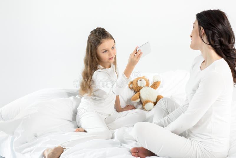 Liten flicka i pyjamas som fotograferar modersammanträde på säng arkivfoton
