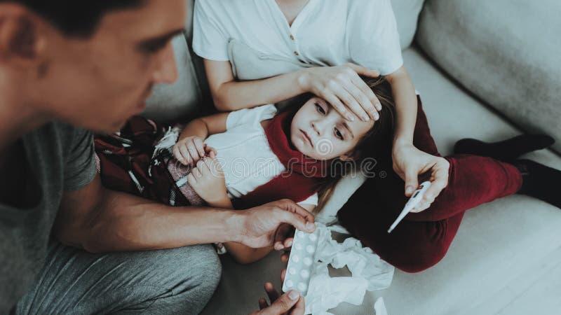 Liten flicka i röd halsduk med förkylning med familjen sjukt barn för flicka Vit soffa i rum Avla och fostra sjukdombegrepp royaltyfria bilder