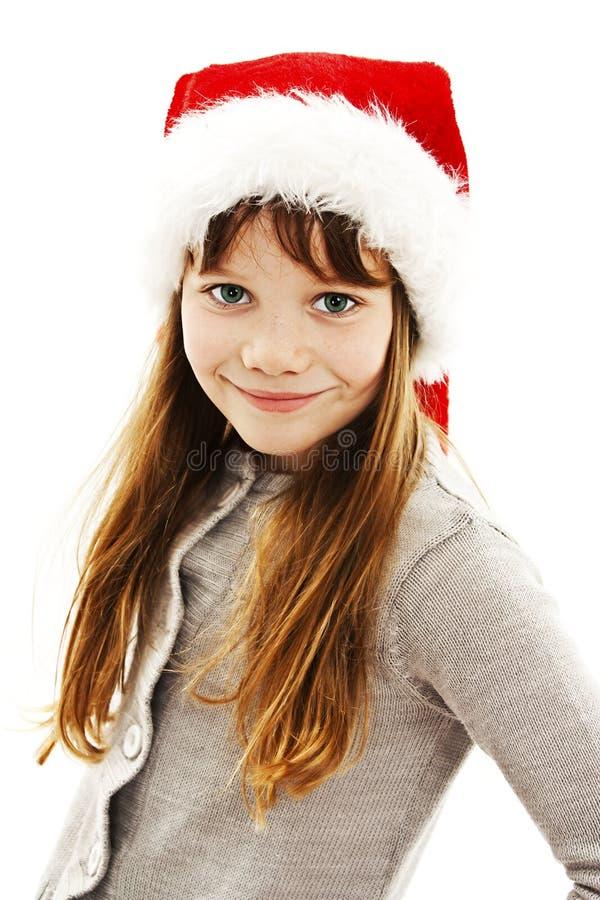 Liten flicka i röd jultomtenhatt. Stående royaltyfri fotografi