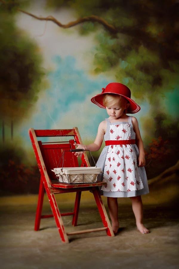 Liten flicka i röd klänning med äggkorgen royaltyfria foton
