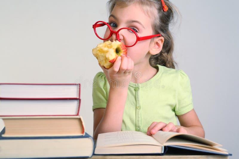 Liten flicka i röda exponeringsglas bitit äpple royaltyfria foton