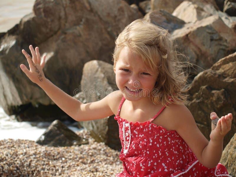 Liten flicka i röda sundress på havet mot en bakgrund av stenar royaltyfri bild