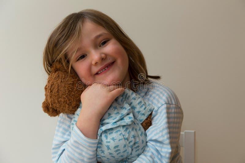 Liten flicka i randig skjorta med smutsigt smutsigt blont hår som kramar hennes nallebjörn arkivfoto