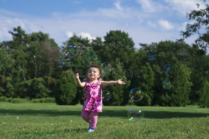 Liten flicka i rosa färgdräkten som fångar bubblor royaltyfria foton