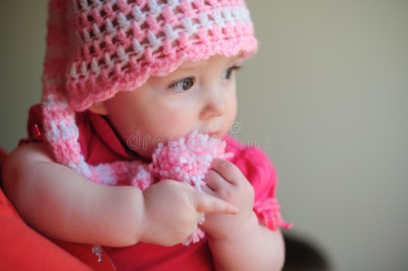 Liten flicka i rosa färger stucken hatt royaltyfria foton