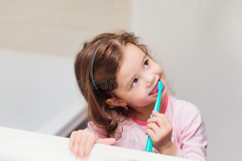 Liten flicka i rosa pyjamas i badrum som borstar tänder royaltyfri foto