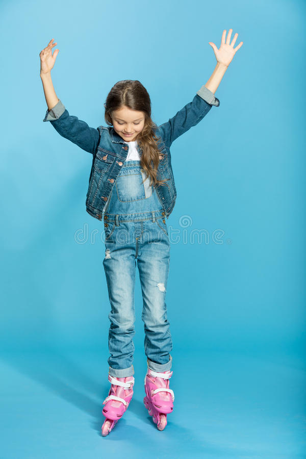 Liten flicka i rosa rullskridskor i studio royaltyfri foto