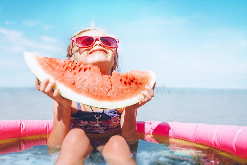 Liten flicka i rosa solglasögon med den roliga ståenden för stort vattenmelonsegment Sund ätabegreppsbild arkivfoton