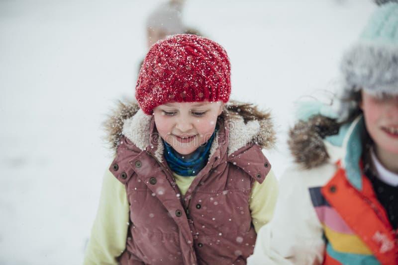 Liten flicka i snön med vänner arkivbild