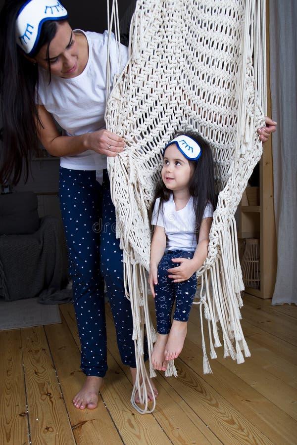 Liten flicka i stolen mamman ser henne med förälskelse arkivfoto
