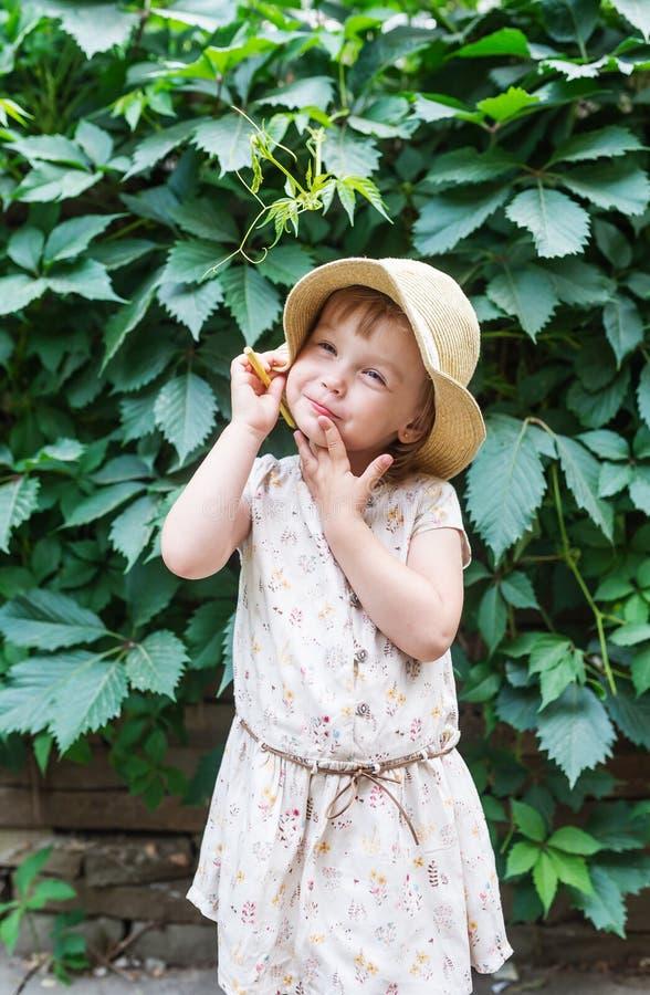Liten flicka i sugrörhatt med den gula blyertspennan på sidor för grön växt för bakgrund i trädgårds- sommar royaltyfri foto