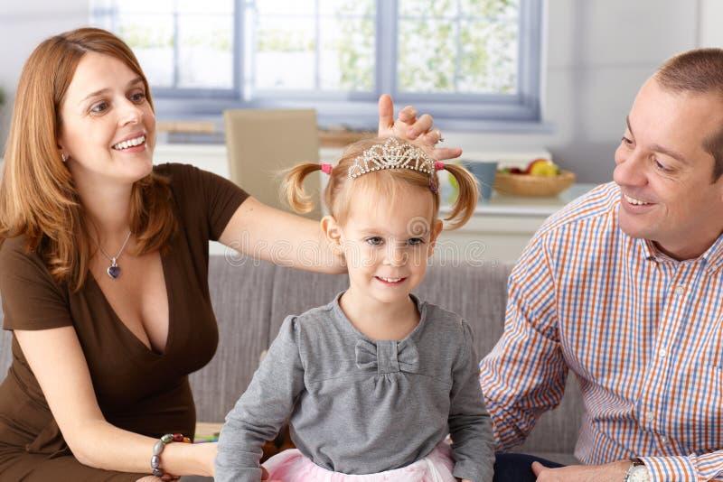 Liten flicka i tiara som ler med föräldrar omkring royaltyfria bilder